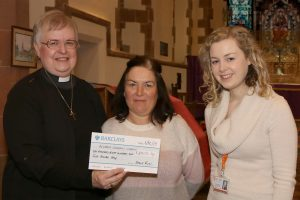 Vicar presenting cheque for Acorns