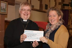 Vicar presenting cheque for school